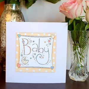 A neutral new baby card with hand drawn illustrations on a peach spotty background and hand stitched edging.