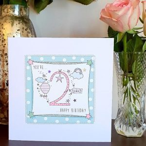 A 2nd birthday card in pinks and blues with a big pink spotty 2 and rainbows, stars and balloons. Hand finished with stitching and silver stars