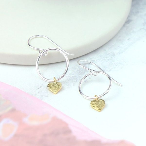 A pair of sterling silver drop earrings which have a hoop design with a scratched gold plated heart on the bottom of it.
