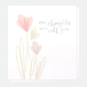 A white card with embossed flowers and gold foiling and the words 'Our thoughts are with you' printed on it.