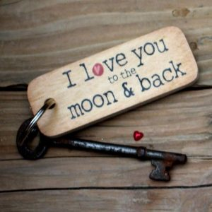 A wooden rustic oblong keyring with the wording I love you to the Moon and Back Printed on it.