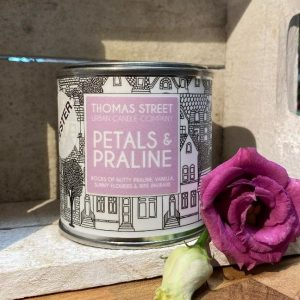 A Thomas Street tin candle with the aroma of petals and praline