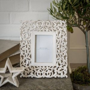A white filigree cut out patterned wooden photograph frame for a 6 x 4 inch photograph. Finished with white distressed paint look
