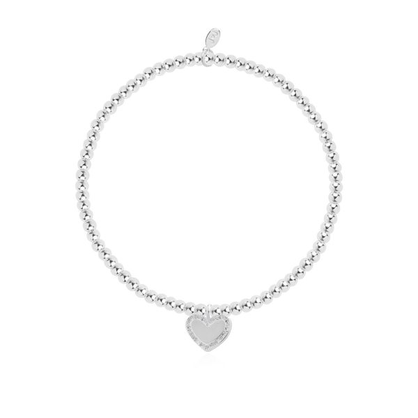 A silver plated bead stretch bracelet with an embellished heart charm from Joma Jewellery. The bracelet is presented on a pink coloured card with the wording A Little Happy Mother's Day printed on it.