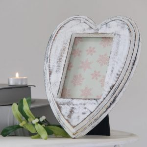 A distressed white paint finish on a heart shaped photograph frame for a 9.5 x 13.5 cm photograph