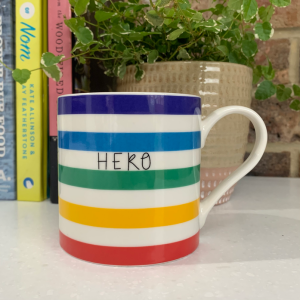 A multi coloured striped bone china mug with the word Hero printed on it. On the inside of the mug a little rainbow is printed.