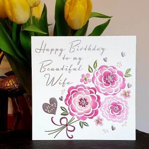 A birthday card for your wife with pink flowers that are embossed and highlighted with foil. A little silver heart with all my love. Happy Birthday to my beautiful wife.