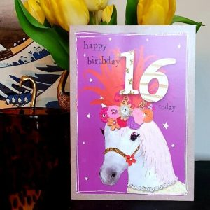 A 16th birthday card with a flamboyant circus horse in a beautiful feathery headress decorated with flowers and little sparkly crystals.
