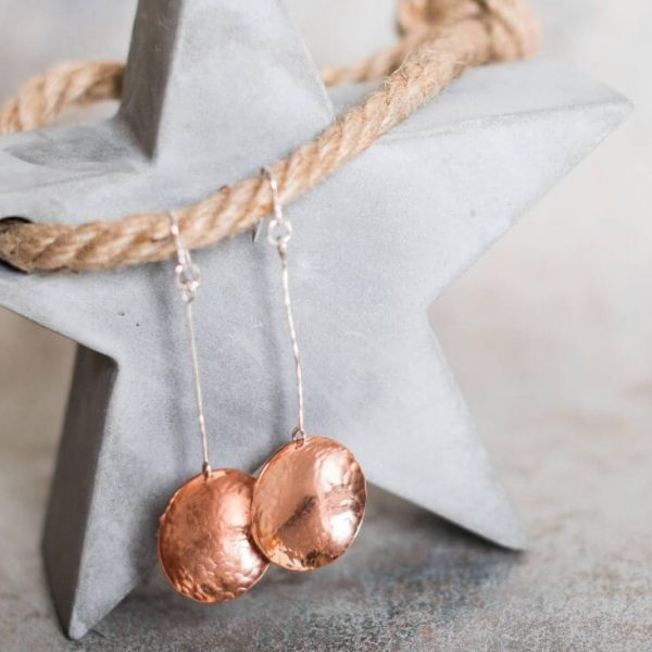 A pair of long drop earrings hand crafted from copper and sterling silver. A long silver wire with a hammered textured copper disc suspended from the end. Presented in a gift box