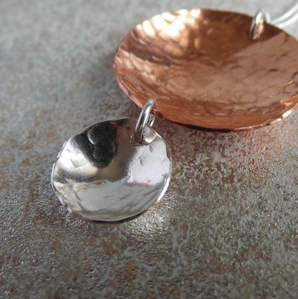 A handcrafted necklace with two hammered discs pendant. A larger copper hammered disc and a smaller sterling silver hammered disc suspended from it. The pendant is on a silver chain.