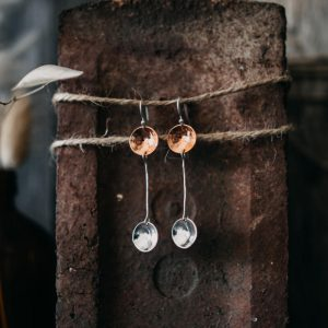 A pair of hand crafted drop earrings in sterling silver and copper. A silver ear wire with a hammered copper disc from with a silver wire extends to hold another hammered silver disc.