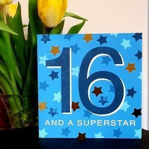 A bright blue card with a big dark blue 16. Embellished with lots of gold and blue stars. 16 And A Superstar.