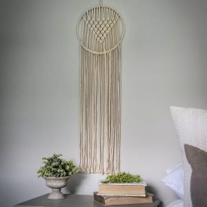 A large hand made macrame dream catcher to hand on the wall. Made with a circular top and long hanging cords. Woven in natural cream rope this beautiful dream catcher is 85cm long