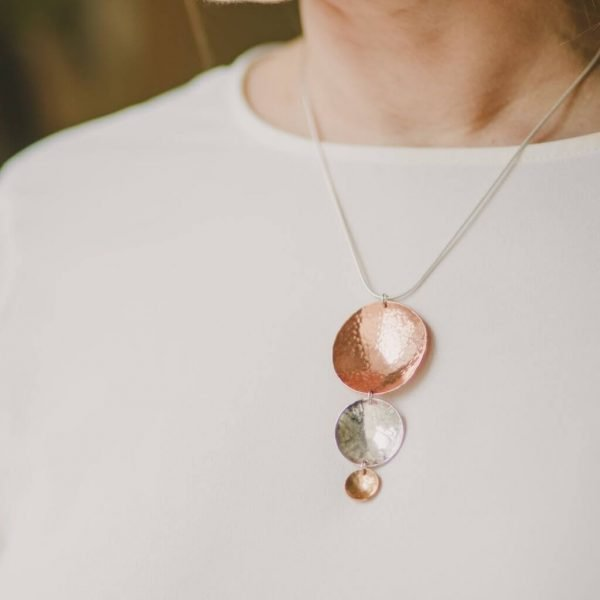 A hand made pendant necklace with 3 hammered discs in decreasing sizes in brass, copper and silver.