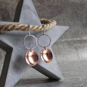 A pair of hand crafted silver and copper mixed metal earrings. A silver ear wire holds a hammered circle of silver with a hammered textured copper disc suspended from it. The earrings have approximately 5cm drop and come in a gift box