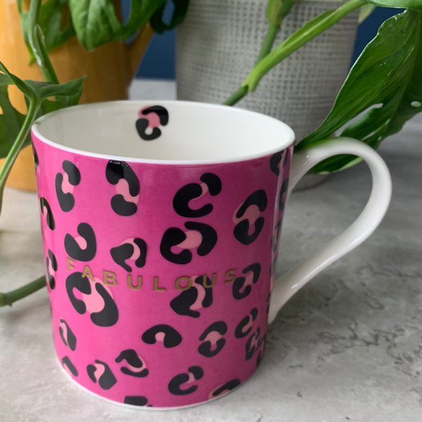 A bone china mug with vibrant pink leopard print design and the word Fabulous printed in gold. On the inside of the mug is a little single leopard print.
