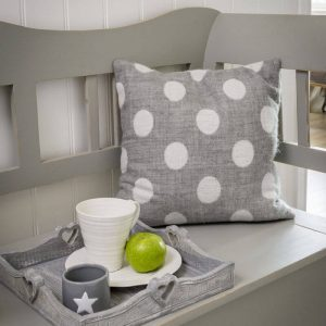A soft woven 40cm square cushion in dove and charcoal grey polka dots. One side is charcoal with dove grey polka dots, the other, dove grey with charcoal polka dots.