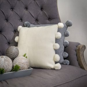 A ivory knitted cushion with 5 grey pom poms on each side. Knitted in a moss stitch. Feather inner.