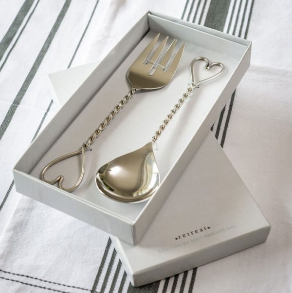 A pair of salad servers with a heart at the end of the handle in a white gift box. A spoon and a fork in shiny nickel with a twisted handle and a heart shaped end.
