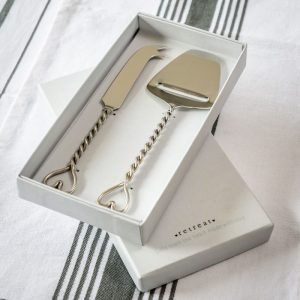 A boxed set of cheese knives with twisted handles with a heart on top. The knife and slice are made of nickel and are presented in a white gift box