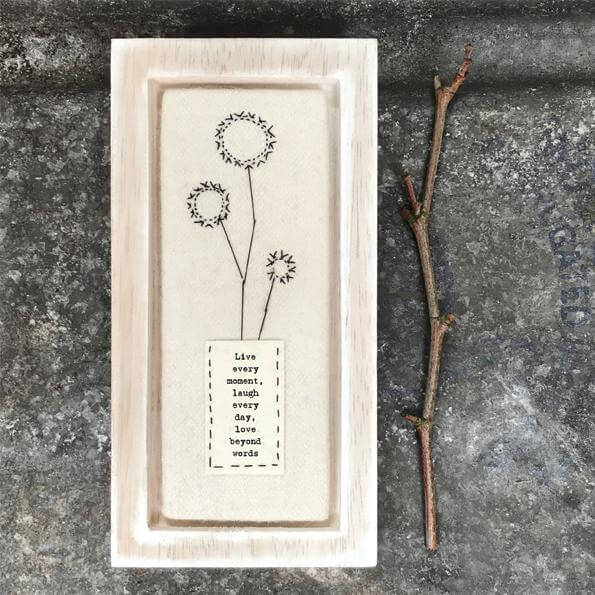 An embroidered cream felt picture in a pale washed wood frame. Embroidered in black thread. The embroidery is of a vase of flowers, the vase has the words Live every moment, laugh every day, love beyond words