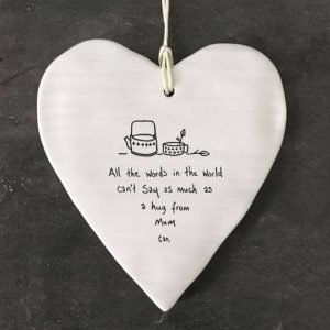 A white ceramic heart with a hanging cord printed with a drawing of a teapot and cup and the words All the words in the world can't say as much as a hug from Mum can