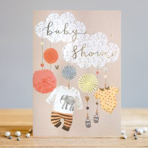 A gorgeous Baby Shower card from card designer Louise Tiler. The card has 2 cute clouds with the words Baby Shower embossed and foiled. There are images of hanging decorations and baby clothes hanging from the clouds.