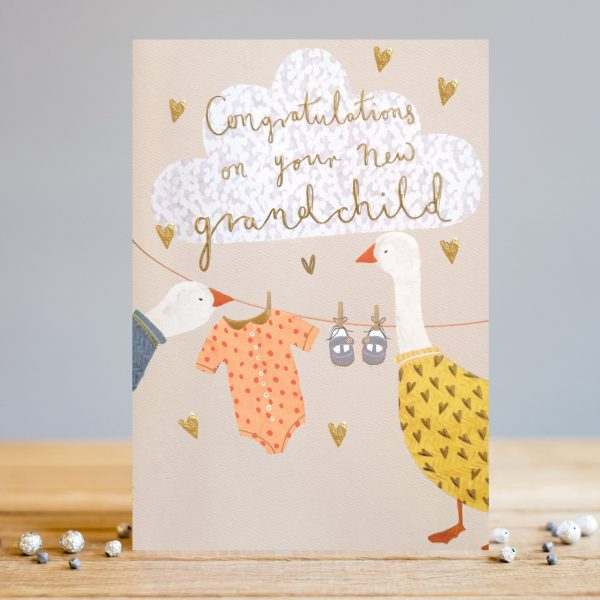 A cute card from Louise Tiler with an image of baby clothes hanging on a washing line with little hearts around it. There are 2 gees looking at the clothing and a large white cloud is above the washing line. The words 'Congratulations on your new Grandchild' are embossed gold foiled and printed on the cloud.