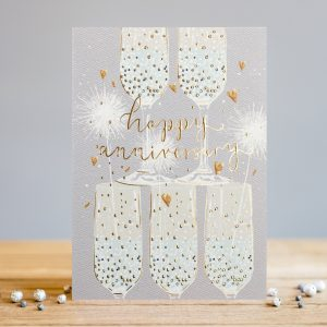 A beautiful card with a stack of champagne glasses with sparkles and hearts all around them. The words Happy Anniversary are embossed, foiled and printed in the centre of the card.