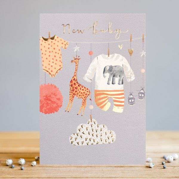 A sweet card from Louise Tiler. A neutral New Baby Card with a pale grey background. The image on the card is of new baby clothes hanging on a washing line along with a cute giraffe toy. The words New Baby are embossed, foiled and printed at the top of the card.
