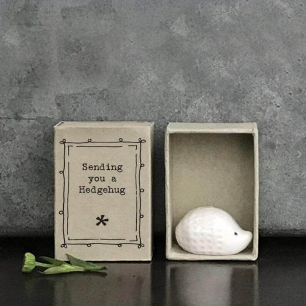 A tiny white ceramic hedgehog in a little grey cardboard matchbox printed with Sending You A Hedgehug