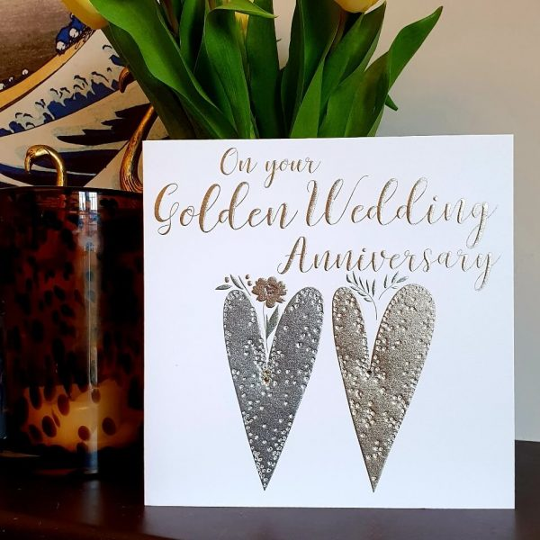 A large luxury 22cm square golden wedding anniversary card. Two foiled hearts with clear crystals embelishments and gold foil words, On your Golden Wedding Anniversary