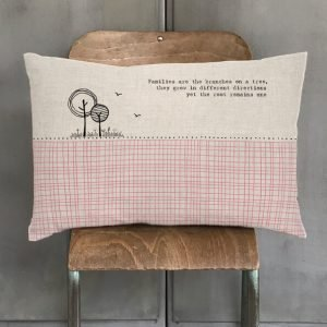 A long cushion with a contemporary design in pink and black and the words, Families are the branches on a tree, they grow in different directions yet the root remains one