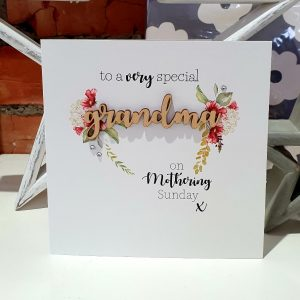 A Mother's day card with a floral design and the word Grandma is cut out of wood. The card says to a very special Grandma on Mothering Sunday