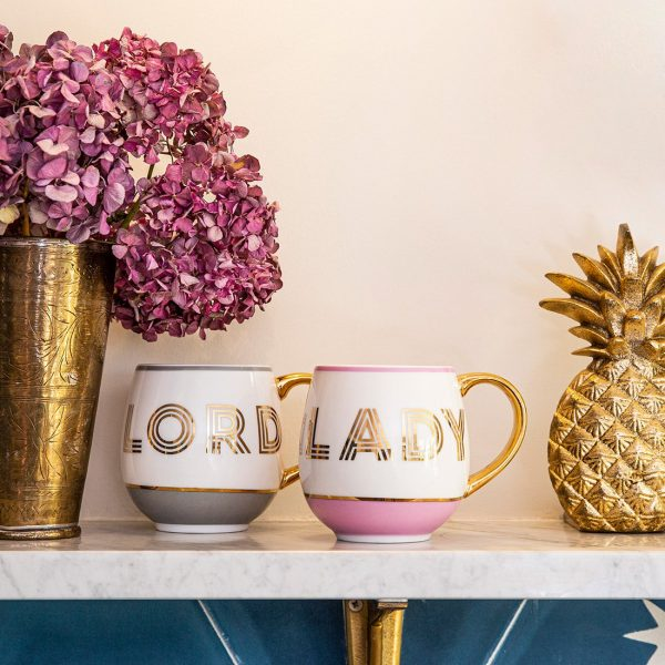 A pair of china mugs from Bombay Duck with the words Lord and Lady printed on them in gold foil.