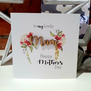 A Mother's day card with a floral design and the word Mam is cut out of wood. The card says to my lovely Mam Happy Mother's Day
