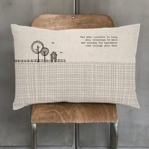 A natural linen long cushion with a feather filled inner. Printed with a modern black and white design of a house and trees and the words May your troubles be less, your blessings be more and nothing but happiness come through your door.