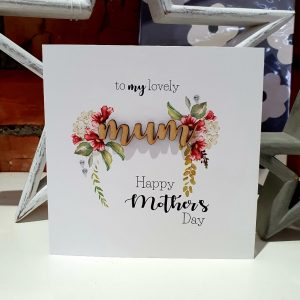 A Mother's day card with a floral design and the word Mum is cut out of wood. The card says to my lovely Mum Happy Mother's Day