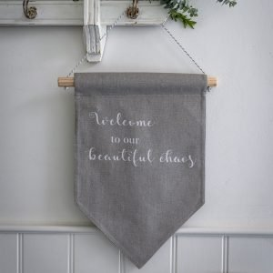 A grey fabric hanging sign with the words 'Welcome to our Beautiful Chaos' printed on it in white.