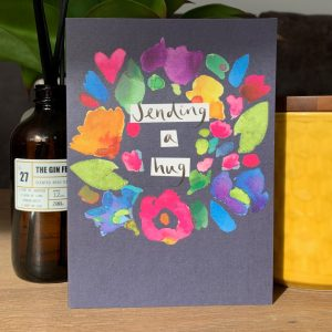 A colourful card from Sarak Kelleher with a dark blue background and colourful leaves flowers and hearts on it and the words Sending a Hug printed on it.