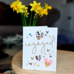 An engagement card with gold and floral print hearts in pinks, teals and gold. Engaged! in gold foil