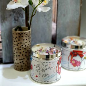 A classic cotton scented candle in a tin with the words With Love on Mothering Sunday
