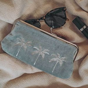A 18cm by 9cm grey velvet pouch with three silver foil palm trees across the front, a silver clip top fastening and a beautiful pink lining.