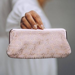 A pink velvet pouch covered in a rose gold heart pattern with a gold clip top fastening and a stunning grey lining