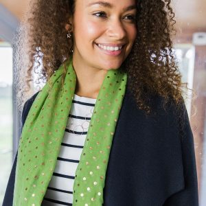A vibrant green lightweight scarf with rose gold polka dots