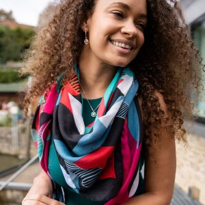 Bold print scarf with oversize graphoic print in a mix of reds, blues, greens and black