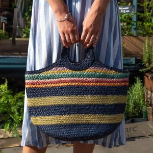 Navy woven jute bag with wide metallic gold stripes, rainbow stripes and round handles