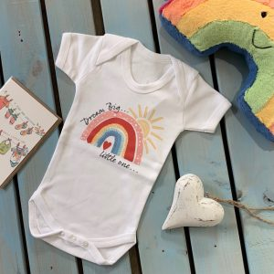 A white soft cotton baby vest with a lovely colourful rainbow design with the words Dream Big Little one printed on i