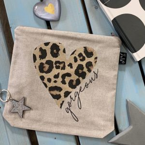 A beige coloured cotton wash bag with a large leopard print bag with metal zip and the word Gorgeous printed on it.