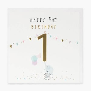 A first birthday card with gold foil and embossed details. A big gold one and a little elephant on a unicycle holding up the one with balloons in his trunk. Some bunting and the words Happy first birthday